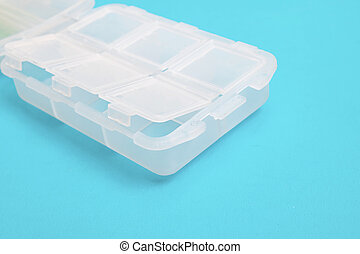 Plastic container for pills on blue background