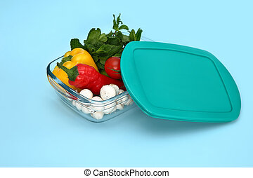 Plastic container with vegetables on blue background