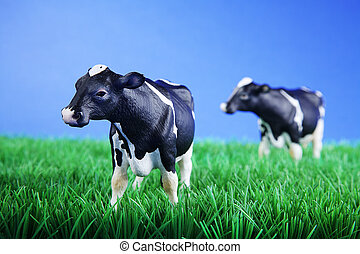 plastic cow on grass