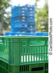 Plastic crates - Green plastic crates. Blurred blue...