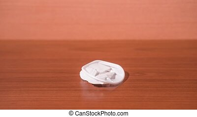 Plastic cup folds into a lump in stop motion on a wooden table