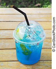 Plastic cup of blue soda with straw on wooden table inthe...