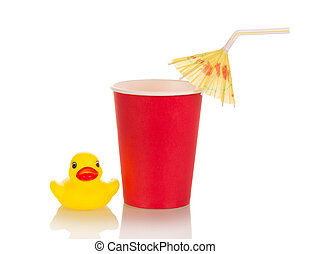 Plastic Cup with cocktail tubule and umbrella next to child's toy, isolated on white