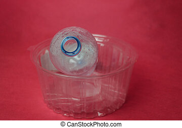 Plastic empty bottle in container on red background, space for text. Concept of environmental pollution by polyethylene