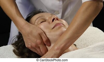 plastic face massage in spa saton. woman enjoys the services of a professional massage therapist. 4K