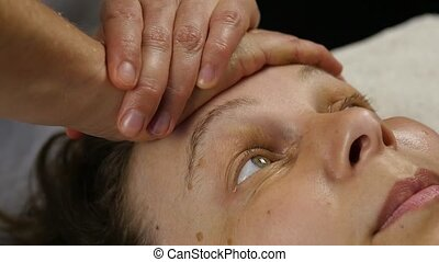 plastic face massage in spa saton. woman enjoys the services of a professional massage therapist. slow motion