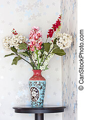 Plastic flowers with ancient vase.