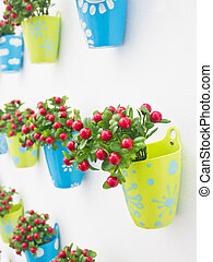 Plastic flowers with colorful plastic vase decorating on the wall.