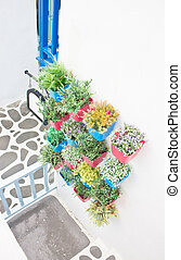 Plastic flowers with colorful plastic vase hang in row on the wall.