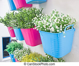 Plastic flowers with colorful plastic vases hang in row on the wall.