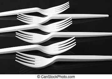 Plastic forks - White plastic forks on black background.