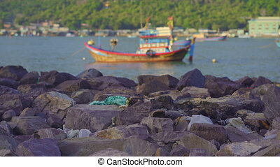 Plastic garbage laying on the rocky seashore with an Asian fisherman village at a background. Plastic pollution concept.