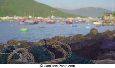 Plastic garbage laying on the rocky seashore with an Asian fisherman village at a background. Plastic pollution concept