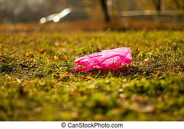 Plastic garbage packet on the green grass