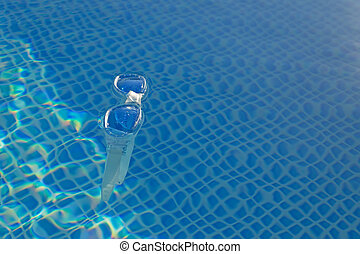 plastic goggle - pool goggle floating in the water