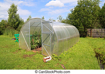 plastic hothouse in summer garden