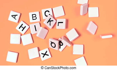 Plastic letters bouncing and showing alphabet on orange...