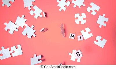 Plastic letters bouncing and spelling out autism next to jigsaw puzzle in slow motion