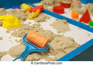 Plastic Mold toys with sand on sandbox. Background blurry.