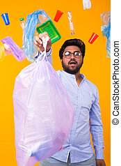 Plastic recycling problem, ecology and environmental disaster concept - Indian man holding garbage bag on yellow background