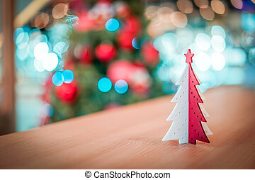 Plastic red and white Christmas tree decoration on the wood table with blur big Christmas tree behide.