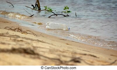 Discarded, plastic soda bottle bobbing in the surf as it floats on the swashline of a tropical beach wilderness. Video 4k