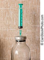 syringe stuck into the bottle