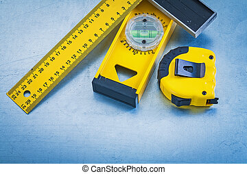 Plastic tape measure wooden construction level and square ruler on metallic background maintenance concept