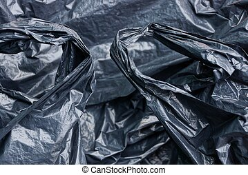 plastic texture of a piece of crumpled black cellophane with handles