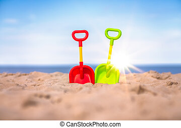 Plastic toy shovels on the beach