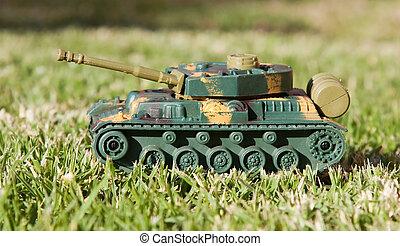 Plastic toy tank on grass