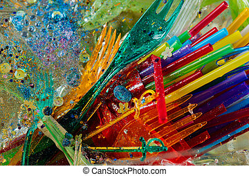Transparent plastic forks being mixed with straws and...