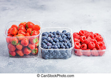Plastic tray container of fresh organic healthy blueberries, strawberries and raspberries on stone kitchen background.