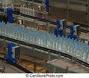 Plastic water bottles on conveyor and water bottling machine...
