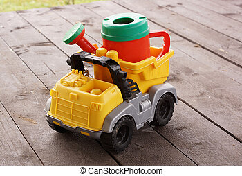 Plastic watering can in the back of the toy car.
