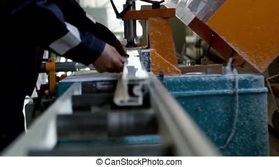 Plastic window and door manufacturing. Worker cutting PVC profile. Plastic window and door manufacturing. Worker cutting PVC profile. Workmen inspecting windows with shutter at workshop indoor.