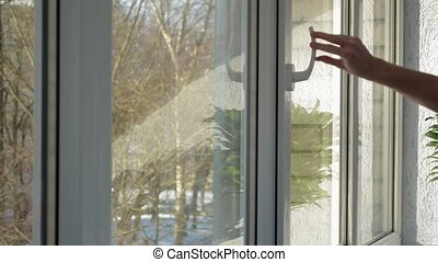 Plastic window is being opened and closed by male hand