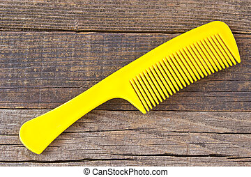 Plastic yellow comb on wooden background