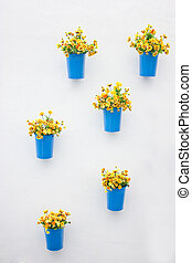Plastic yellow flowers with metal blue vase hang in row on the wall.
