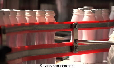 Plastic yogurt bottles in a continuous line ride on a figurative conveyor line