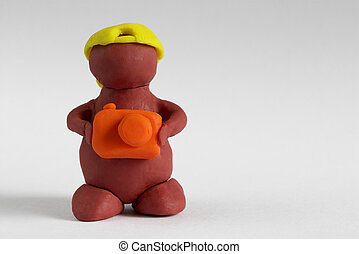 Plasticine man keeping the camera over grey gradient background