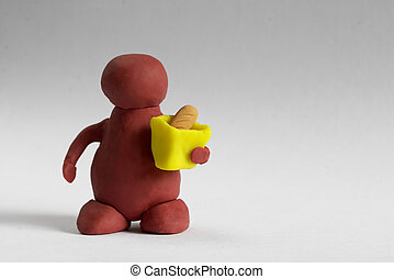 Plasticine customer keeping a bag with a bread over grey background