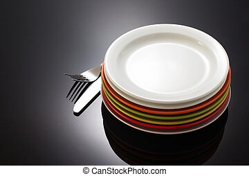 plate and fork with knife on black