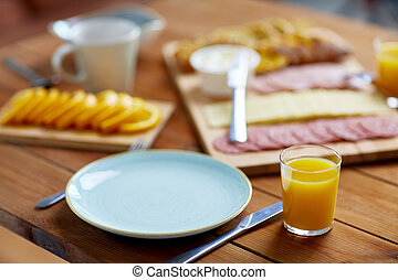 plate and glass of orange juice on table with food