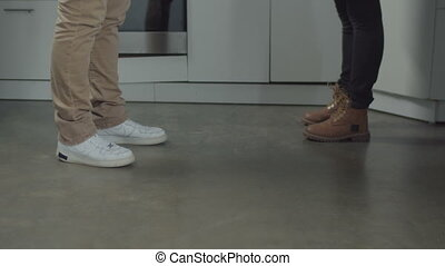 Close-up of white plate breaking into small pieces while falling on kitchen floor during couple swearing symbolizing breakup of family. Family relationships do not glue like broken plate.