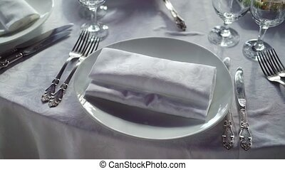 Plate, cloth napkin, knife and fork on white cloth on table in restaurant
