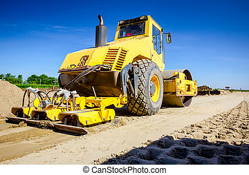 Plate compactor is mounted on road roller to compact soil at...