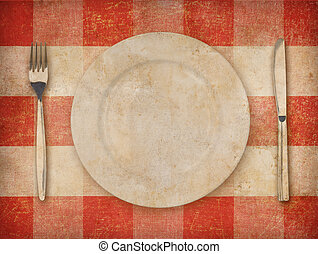 Plate, fork and knife over grunge tablecloth background