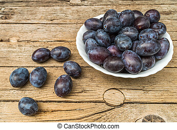 Plate full of fresh plums on a wood