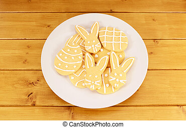 Plate full of frosted Easter cookies on a wooden table